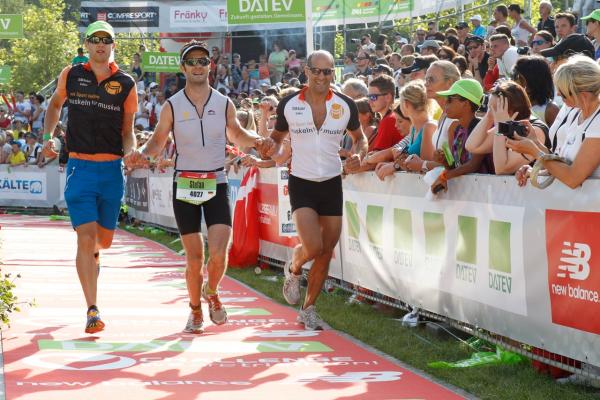 Die DFS - Muskeln für Muskeln-Staffel beim Zieleinlauf: Manuel Lohr (Towerlotse München) 3,8 km Schwimmen (links), Volker Moller (Towerlotse München) 180 km Radfahren (rechts) und Stefan Wolf (Centerlotse Karlsruhe) 42 km Laufen (Mitte)